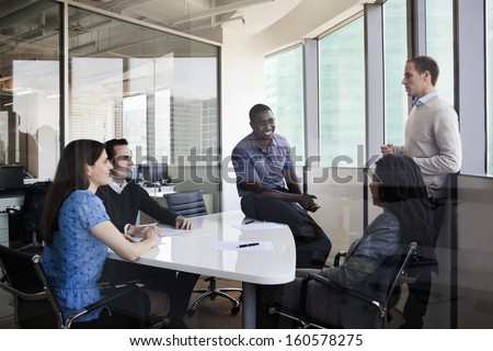 Five business people sitting at conference table and discussing during business meeting - stock photo