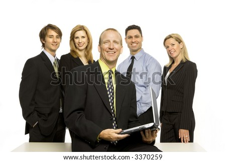 Five business people stand proudly near a desk