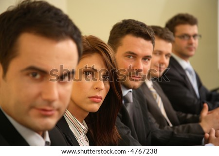 Five business persons in suits sitting at a conference table, taking part in a meeting and/or presentation. focus on woman - stock photo