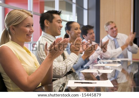 Five businesspeople at boardroom table applauding and smiling