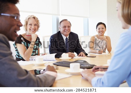 Five Businesspeople Having Meeting In Boardroom - stock photo