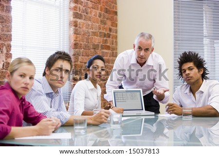 Five businesspeople in boardroom with laptop - stock photo