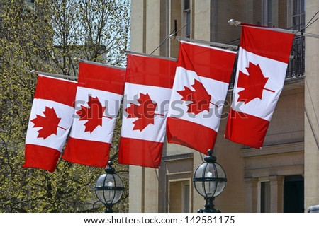 Five Canada national flags hanging from embassy building in Trafalgar Square London England UK - stock photo