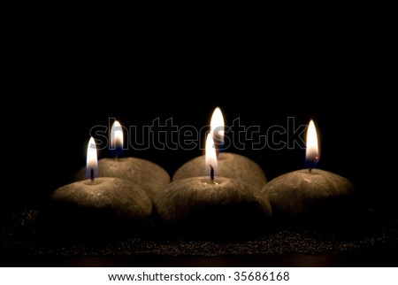 Five candles in the form of stones on a black background
