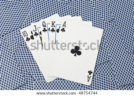 Five cards, showing a royal flush with clubs from ten to ace, on a background of backsides of blue playing cards - stock photo