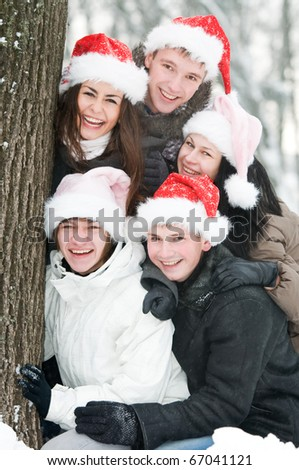 five cheerful young people in rad hats at winter outdoors - stock photo