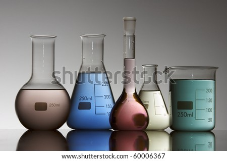 five chemical laboratory flasks containing liquid shiny color