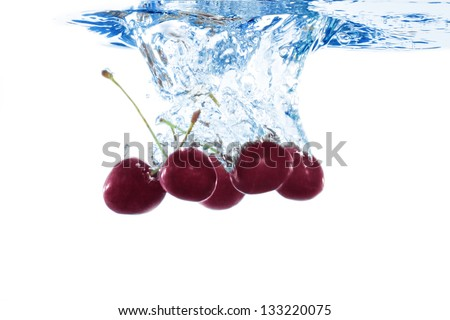 five cherries splashing in water - stock photo