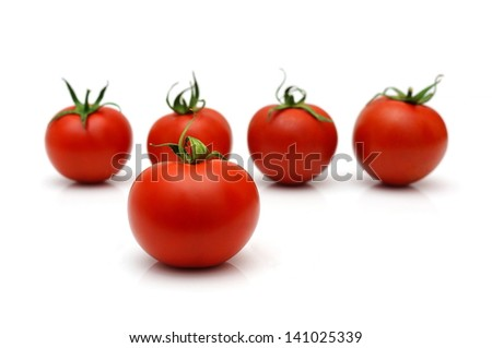 five cherry  tomatoes with four in blur - stock photo