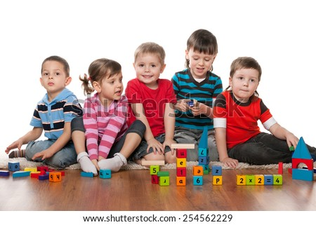 Five children are playing on the floor in the kindergarten - stock photo