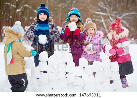 Five children build wall from snow bricks in winter park - stock photo