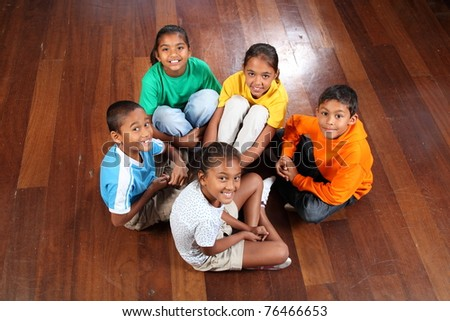 Five children sitting on classroom floor