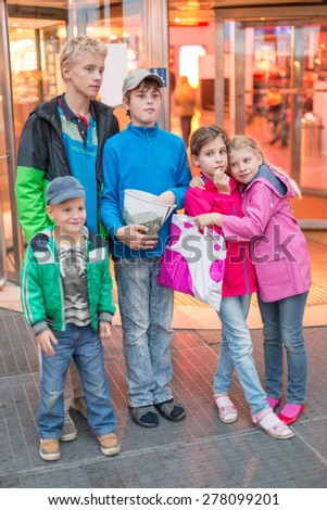 five children stand in front of the mall - stock photo