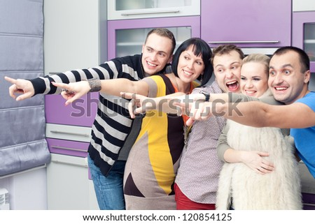 Five close friends enjoying a social gathering together and happy to see something or somebody else at home (kitchen room). Indoor shot. - stock photo