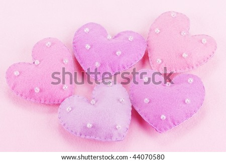 Five cloth hearts on a fiber textured background