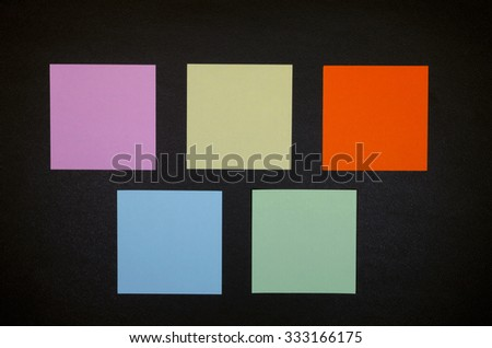 Five colored empty reminders on a black panel - stock photo
