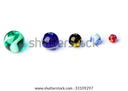 Five colored glass balls known as marbles, on white - stock photo