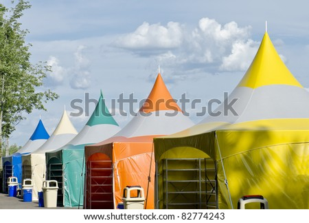 Five colorful carnival tents against a blue cloudy sky.