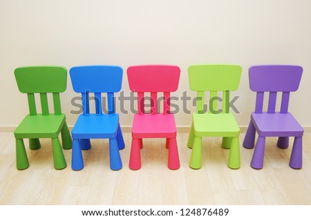 Five colorful chairs in Montessori Kindergarten Preschool Classroom - stock photo