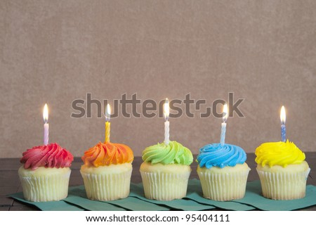 Five Colorful Cupcakes placed on green napkins with lit candles.   Brown stucco background.
