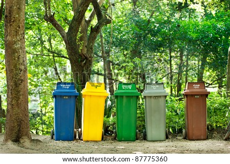 five colors recycle bins in  forest - stock photo
