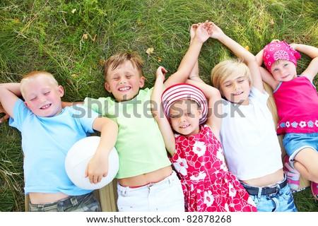 Five cute children lying in green grass and enjoying summertime - stock photo