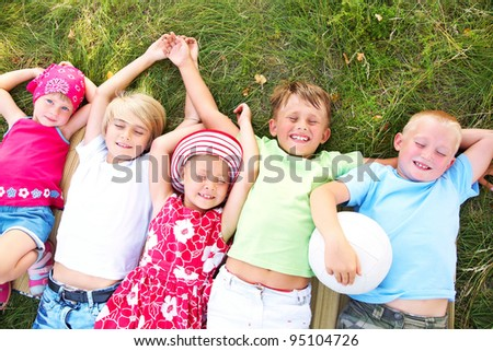 Five cute children lying in green grass and enjoying summertime