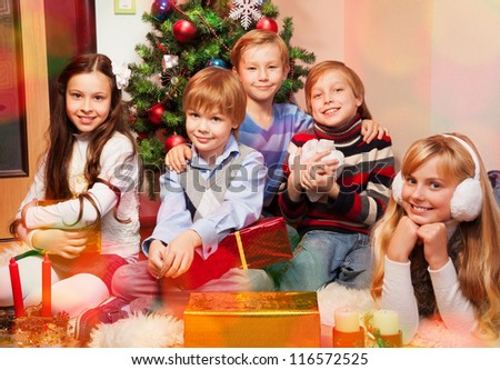 five cute kids sitting near Christmas tree ready to celebrate
