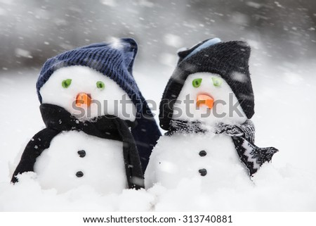 Five cute little snowman in a row, caught in a light snow shower. All wearing hats and scarfs with a carrot for a nose. Winter trees in the background. - stock photo