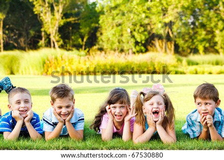 Five cute preschoolers laughing on the grass