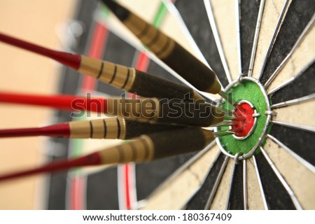 Five darts hitting bullseye on dartboard  - stock photo