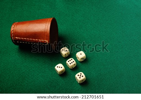 Five dice form cross and a leather cup on green cloth -concept of believe - stock photo
