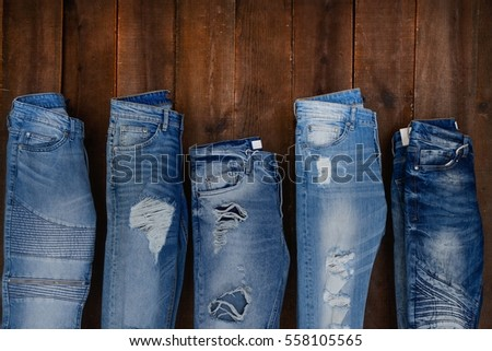 Five different blue denim jean on wood background