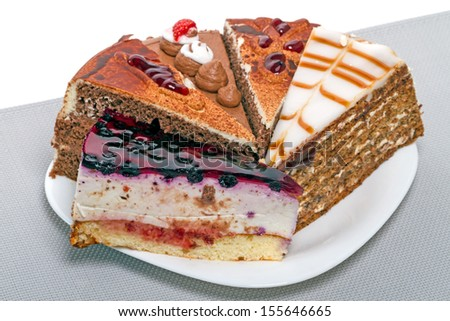 Five different pieces of cake on a white plate - stock photo
