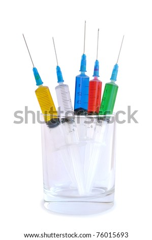 Five disposable syringes in a glass against white background