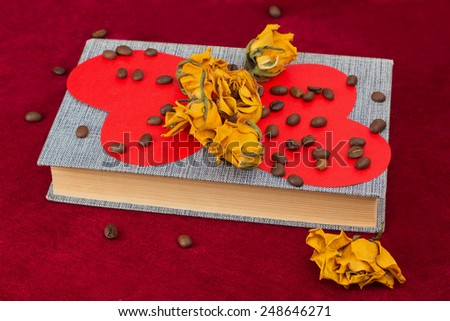 Five dried yellow roses and two red paper hearts lying on the book with coffee beans - stock photo