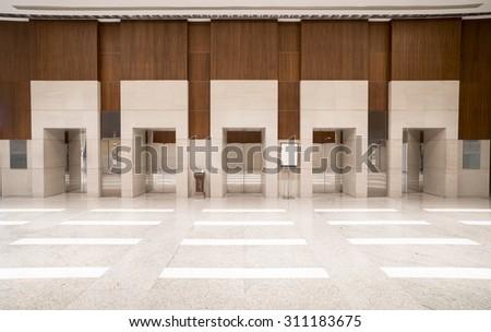 Five elevator doors in office building. - stock photo