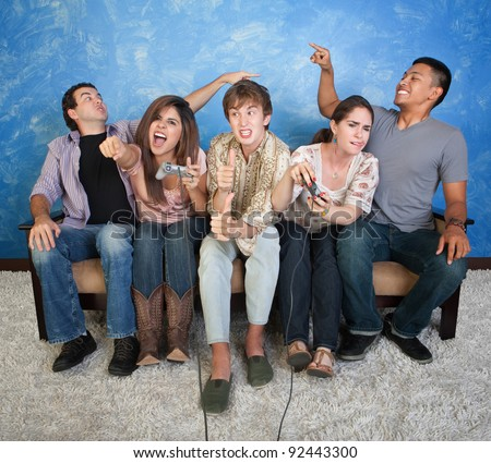 Five excited friends on couch play video games - stock photo