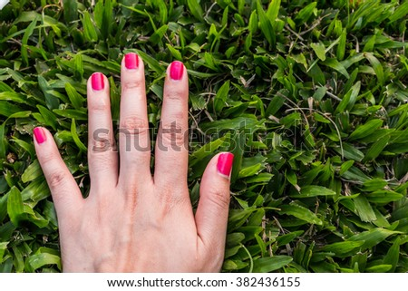 Five fingers is pink nail on green background - stock photo