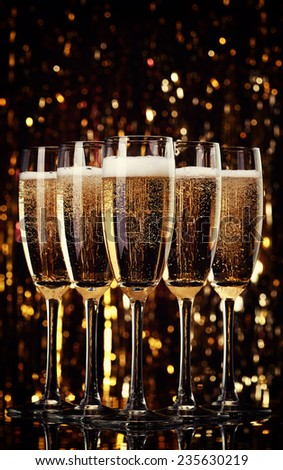 Five flutes of champagne on bokeh background - stock photo