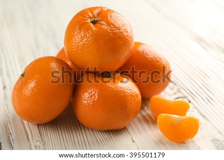 Five fresh delicious unpeeled tangerines with slices on the white wooden table, close up