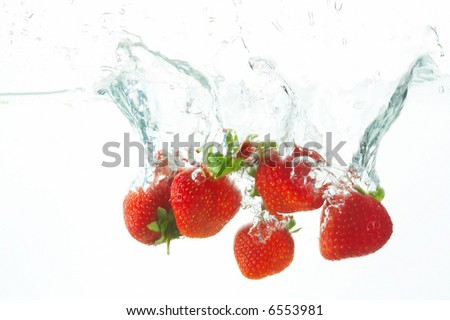 five fresh strawberries falling into the water