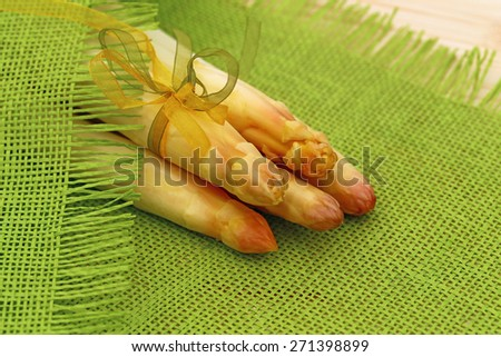 Five fresh white peeled asparagus with green and yellow bow  on green natural burlap fabric texture  background - stock photo