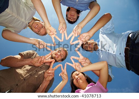 Five friends connecting their hands to star shape