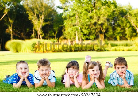 Five friends lying on grass - stock photo