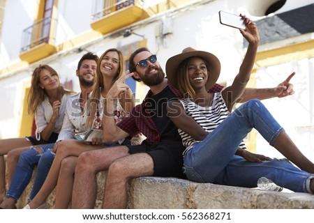 Five friends sitting on a wall in Ibiza taking a selfie