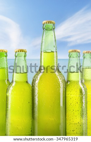 Five full bottles of cold and fresh beer, shot on the beach under blue sky
