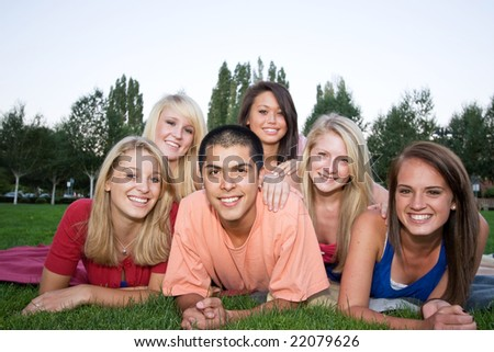Five girl students and one boy lying on the grass smiling in a park. Horizontally framed photo.