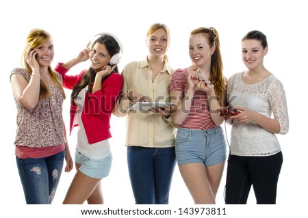 Five girls standing together, each is busy with another activity: use your cell phone, listen to music with headphones, tablet pc, filing nails with a nail file and plays video games. Isolated