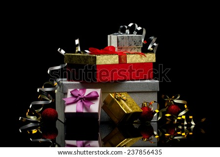 five glamour  gift boxes with bows and bright red balls on black reflection  background - stock photo